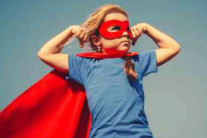 young girl wearing super hero cape and mask